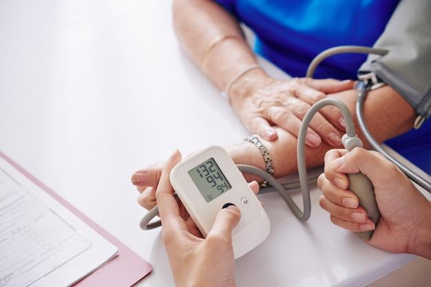 Measuring blood pressure of elderly woman