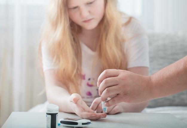 グルコメーターで十代の少女の血糖値を測定する