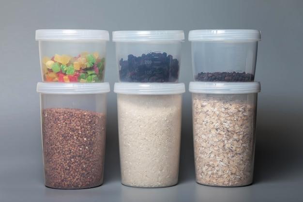 灰色の背景に食品を含むバルク製品を保管するための1000および400立方体の測定缶。食品やバルク製品を保管するための透明なプラスチック容器。瓶に入ったシリアルとバルク製品