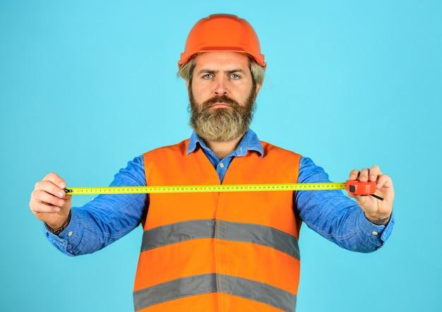 測定の概念。ヘルメットのひげを生やした男。残忍な流行に敏感な労働者は巻尺を使用します。制服を着た男が制作に取り組んでいます。産業の近代技術。テープ付きビルダー。黄色の巻尺。