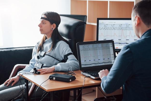 Измерение частоты сердечных сокращений. девушка проходит детектор лжи в офисе. задавать вопросы. проверка на полиграфе
