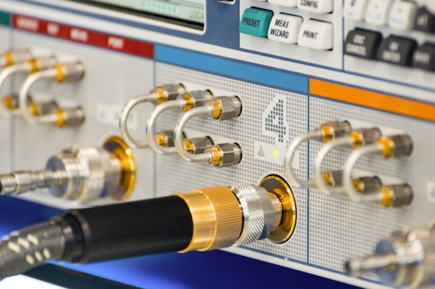 Измерительная высокочастотная аппаратура. в приборную панель вставлены специальные высокочастотные разъемы. абстрактный промышленный фон.