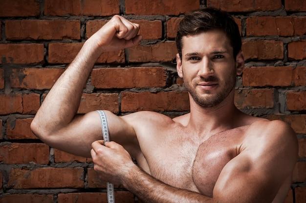 彼の完璧な二頭筋を測定します。測定テープで上腕二頭筋を測定する笑顔の筋肉の男