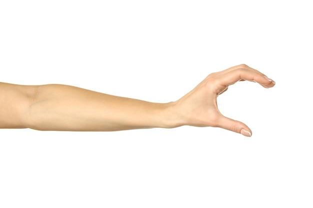 見えないものを測る。白い背景で隔離のフランスのマニキュアジェスチャーと女性の手。シリーズの一部