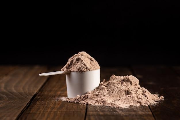 밀크 쉐이크를 준비하기 위해 나무 테이블에 유청 단백질의 국자를 측정합니다.