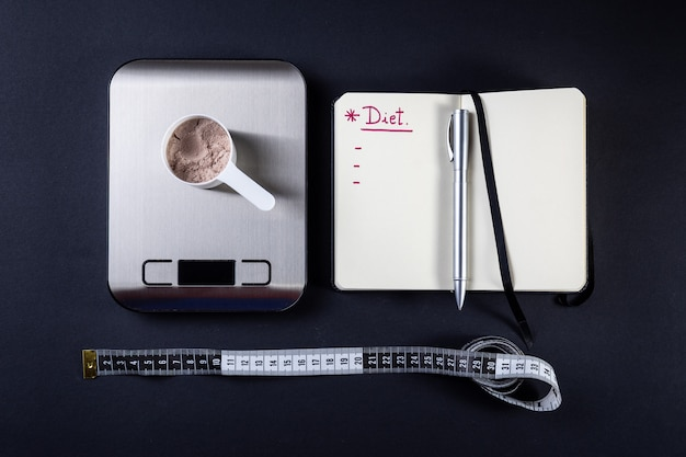 Measuring scoop of whey protein, notebook, weight scale and measuring tape for diet.
