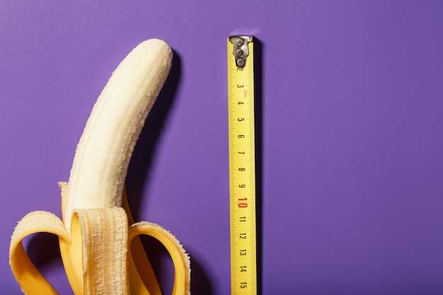 Measuring the size of a banana with a ruler from a roulette wheel on a purple background, as a symbol of a male penis.