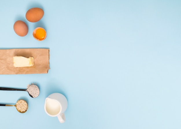 Measuring spoon with oat barn; flour; eggs; butter and milk on blue backdrop
