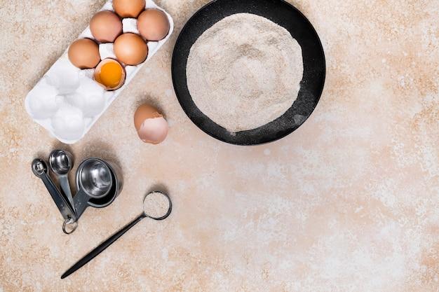 エンバク納屋でスプーンを測定する。小麦粉;ベージュ色の背景上の卵のカートン