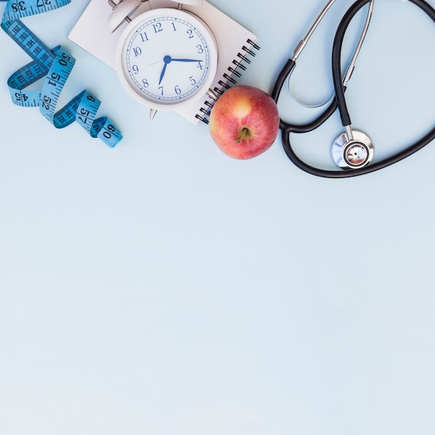 Measuring tape; alarm clock; spiral notepad; apple and stethoscope on blue background with copy space for writing the text