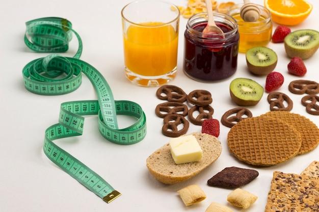 Мерная, лента и тыквенные семечки, миндаль, апельсиновый сок, сыр бри для энергетического завтрака. здоровое диетическое питание. белая поверхность. вид сверху