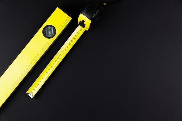 Измерительная лента и строительный уровень желтого цвета на черном фоне