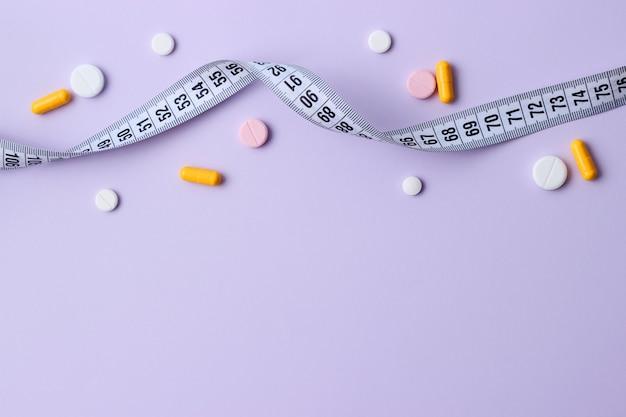 컬러 배경 근접 촬영에 테이프와 다이어트 약을 측정