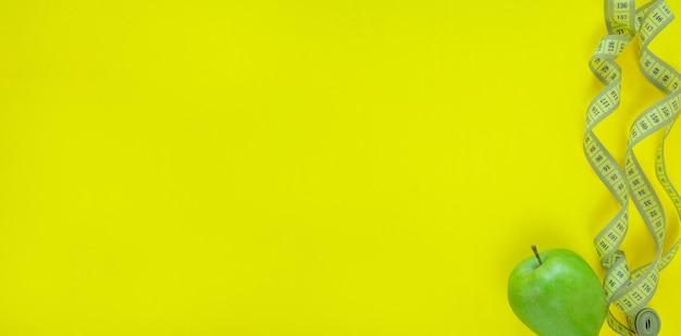 黄色の背景に巻尺と青リンゴ。健康とダイエット食品のコンセプト。上面図、