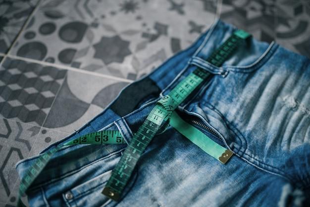 Измерительная лента и джинсы, концепция диеты для похудения. сжигание калорий, диета