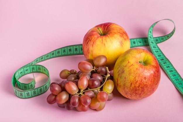 ピンク色のスペースに測定テープとジューシーなフルーツ。ダイエットと減量の概念。