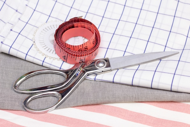 測定テープとはさみは綿生地にあります。縫製コンセプト、天然生地から縫製。