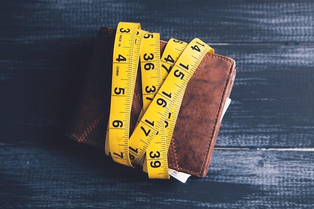 Рулетка и бумажник на столе