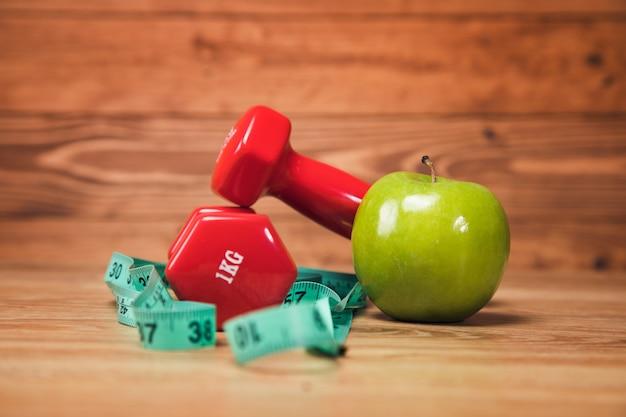 テーブルの上の巻尺、リンゴ、ダンベル
