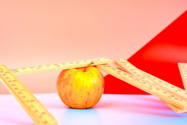 Measuring tape next to an apple, concept of weight loss with healthy diet.
