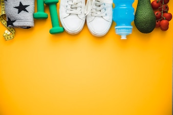 Measuring tape; armband; dumbbells; shoes; water bottle avocado and cherry tomatoes on yellow background