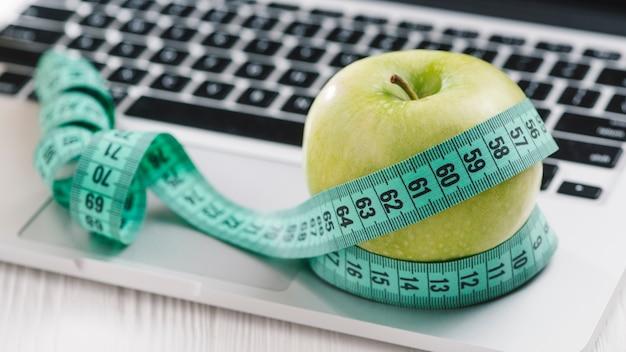 開いているラップトップ上の緑の新鮮なリンゴの周りの測定テープ