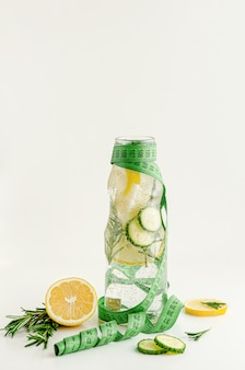 Measuring tape and a bottle of infused water with lemon,cucumber and rosemary. dieting and fat burning concept