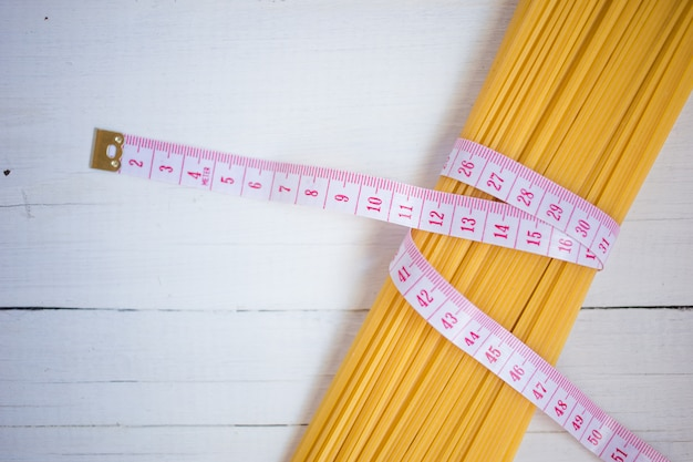 Measuring tape, diet theme. with bunch of uncooked italian pasta spaghetti
