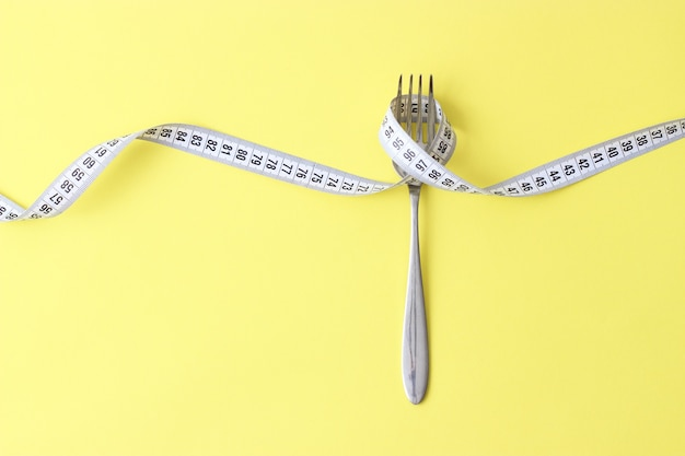 Measuring tape and fork on a colored background top view closeup