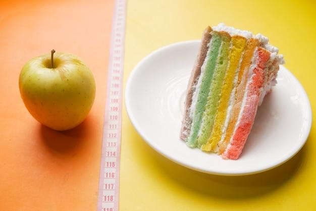 측정 테이프 녹색 사과 및 색상 표면에 빵집 케이크