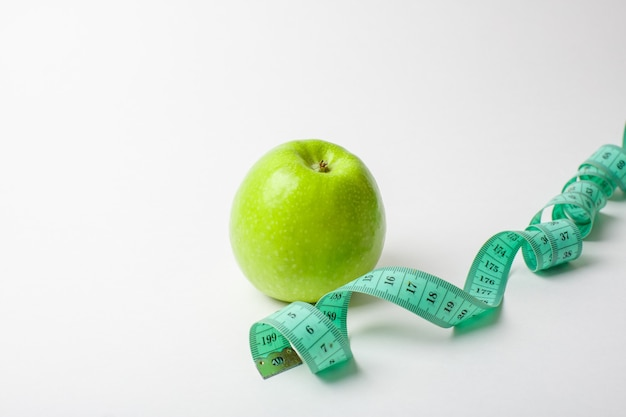 Measuring tape and a green apple on a white background