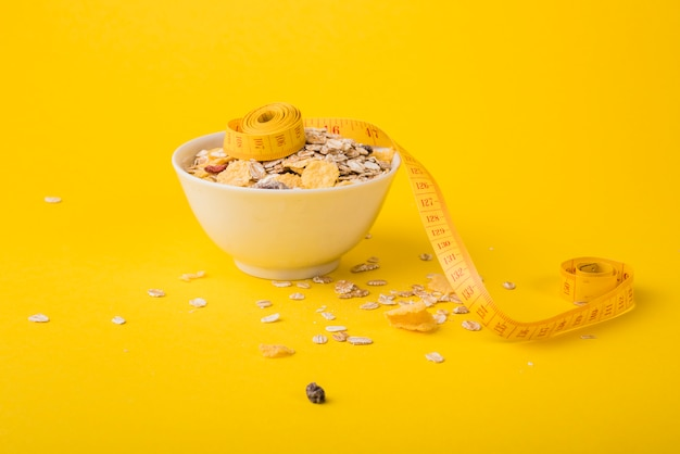 Measuring tape near bowl of muesli