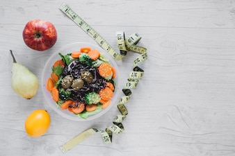 Measuring tape near salad and fruits