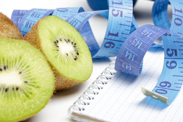 Measuring tape, notebook and kiwis