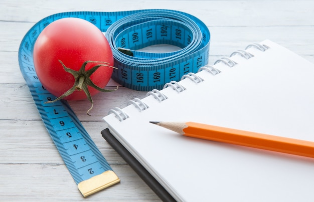 Measuring tape and notebook with juicy tomatoes, the concept of healthy eating and losing weight