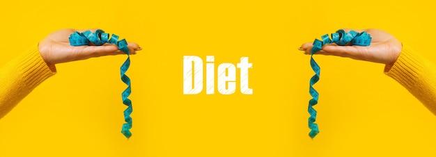 黄色の背景、ダイエット碑文とパノラマ画像の上の手に巻尺を測定