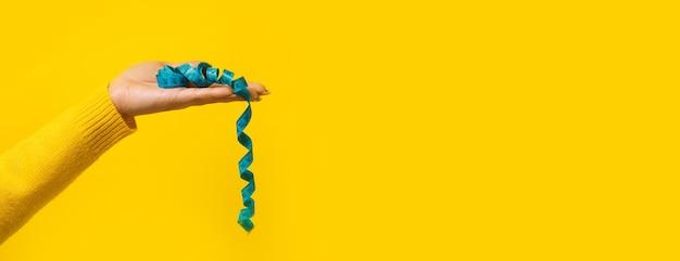 黄色の背景、パノラマのモックアップ、痩身の概念の上に巻尺を測定