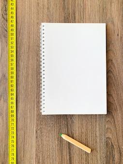 건강한 피트니스를 위해 책 일기 메모장과 펜으로 나무에 테이프를 측정