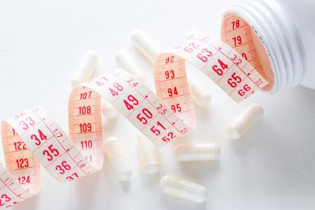 Measuring tape in a pills bottle on white
