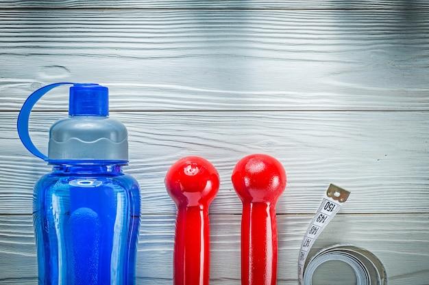Измерительная лента пластиковый шейкер красные гантели на деревянной доске фитнес-концепции