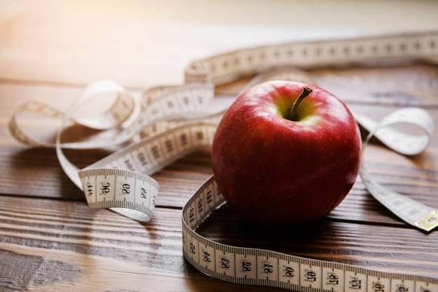 Measuring tape and red apple on wooden background