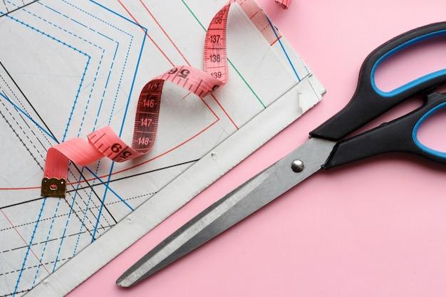 ピンクの背景のクローズアップ、トップビューで縫うための測定テープ、はさみ、縫製パターン。
