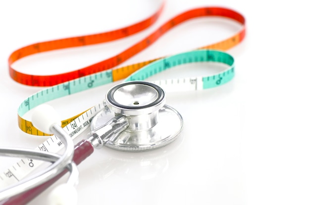 Measuring tape and stethoscope in weight and waist control concept.