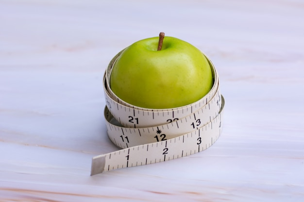 Measuring tape with green apple on white marble background