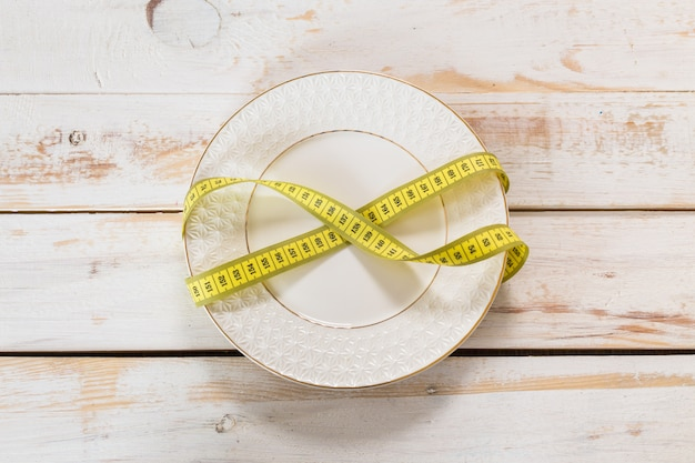 Measuring tape on a wooden background. diet