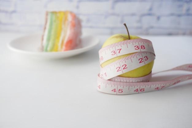 표면에 녹색 사과와 빵집 케이크를 감싸 측정 테이프