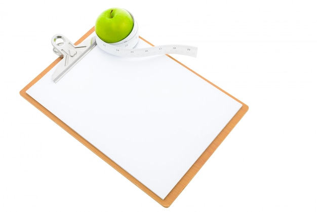 Measuring tape wrapped around a green apple and clipboard
