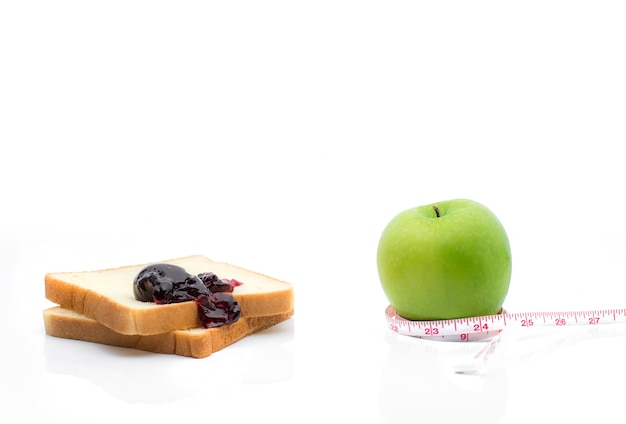 Measuring tape wrapped around a green apple with slice of white bread as a symbol of diet