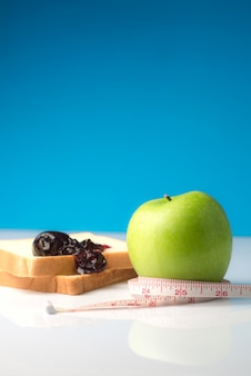 Measuring tape wrapped around a green apple with slice of white bread