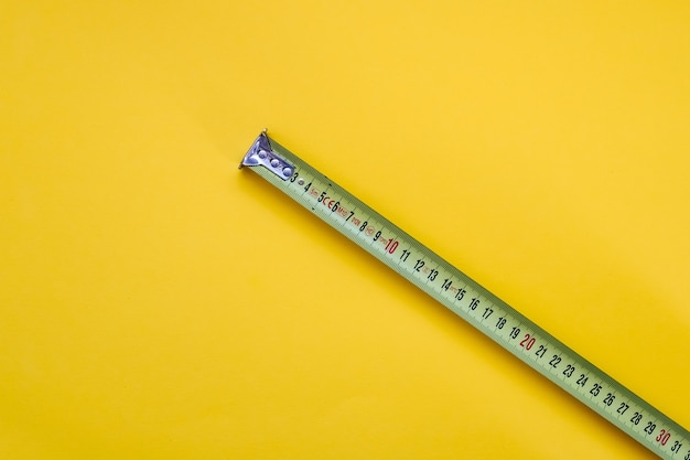 Measuring tape on yellow background.